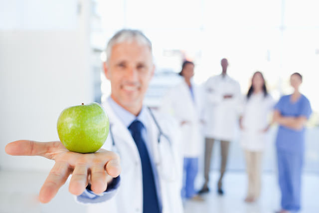 bigstock-Green-apple-held-by-a-doctor-w-39323254