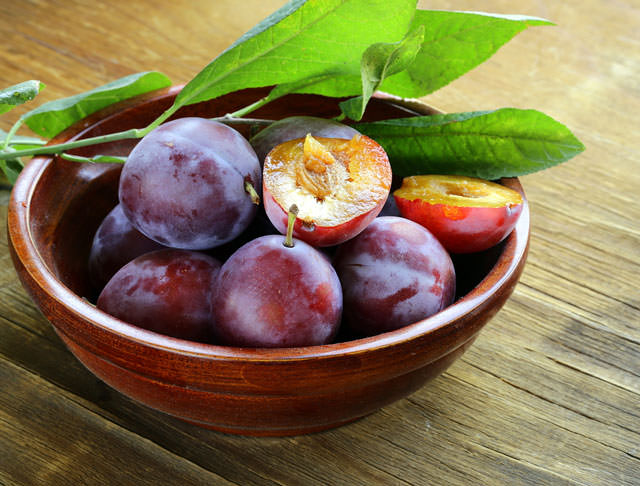 bigstock-ripe-purple-plums-on-a-wooden--50164028