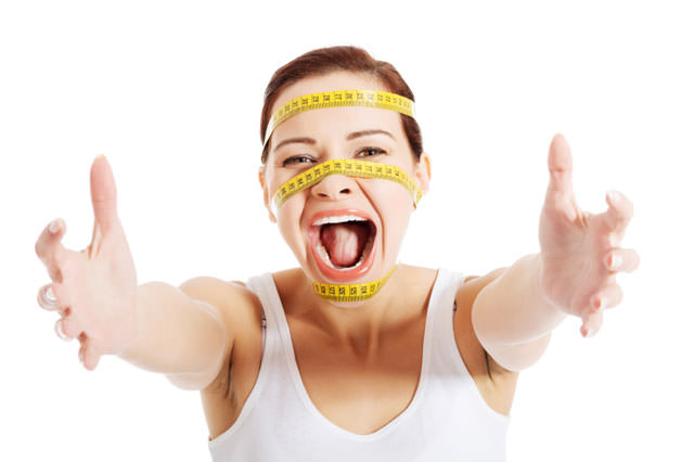 Beautiful woman's face with measuring tape.