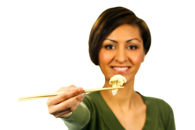 Young woman holds a piece of cauliflower with chopsticks