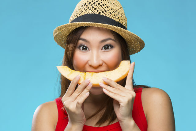 Happy Chinese Woman holding fruit on colorful background.
