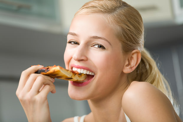 Portrait of young woman with pizza at kitchen