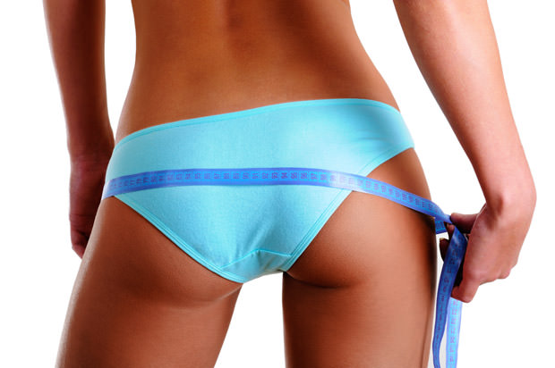 Female buttocks with a measurement tape