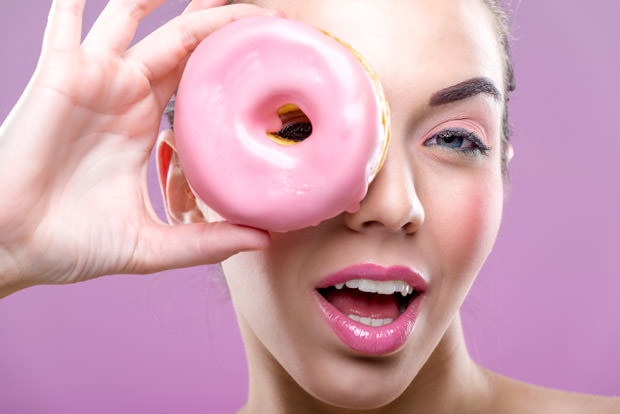 Beautiful woman with donuts, one eye than have a pink donut