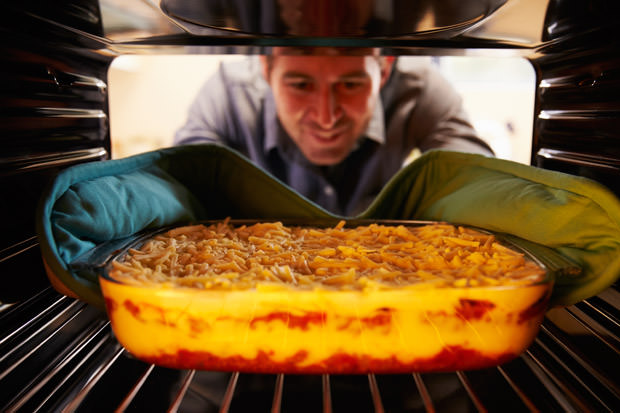 Man Putting Dish Of Lasagne Into Oven To Cook